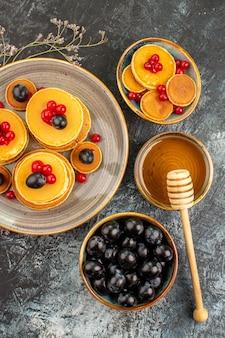 Vertikale ansicht des leckeren frühstücks mit klassischen pfannkuchen, die mit honig und schwarzkirsche serviert werden