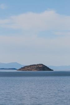Vertikale ansicht des meeres, das tagsüber eine insel unter dem bewölkten himmel umgibt