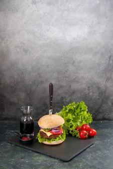 Vertikale ansicht des messers im köstlichen fleischsandwich und im grünen pfeffer auf ketchup-tomaten der schwarzen tablettsauce mit stiel auf grauer oberfläche