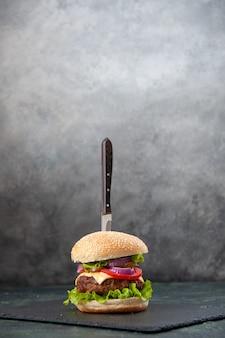 Vertikale ansicht des messers im köstlichen sandwich auf schwarzem tablett auf isolierter unscharfer grauer oberfläche