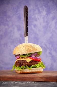 Vertikale ansicht des messers im leckeren fleischsandwich auf hölzernem schneidebrett auf isolierter eisoberfläche