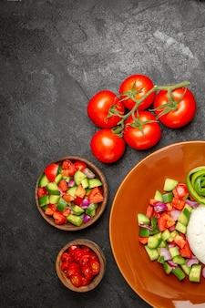 Vertikale ansicht des veganen abendessens mit reis und verschiedenen gemüsesorten auf schwarzem tisch