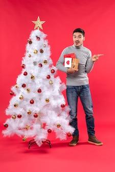 Vertikale ansicht des verwirrten gutaussehenden mannes, der nahe dem verzierten weißen weihnachtsbaum steht und seine geschenke hält