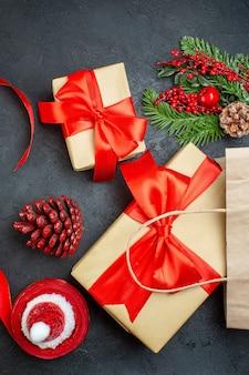 Vertikale ansicht einer rolle der roten band-nadelbaumkegel und der geschenk-tannenzweige auf dunklem hintergrund
