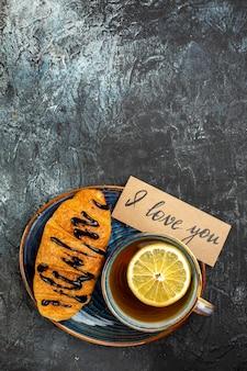 Vertikale ansicht einer tasse schwarzen tees köstliches croisasant für geliebte auf dunklem tisch