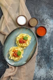 Vertikale ansicht eines blauen tellers mit köstlichen pastagerichten, serviert mit tomaten und fleisch auf einem braunen handtuch zum abendessen mit verschiedenen gewürzen