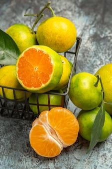 Vertikale ansicht eines korbes voller frischer grüner mandarinen und halbierter mandarine auf grauem hintergrund