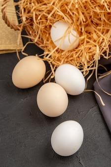 Vertikale ansicht vieler bio-eier innerhalb und außerhalb eines korbes auf einer alten zeitung auf schwarzem handtuchseil auf dunklem hintergrund