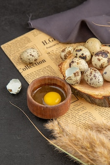 Vertikale ansicht von bio-eiern in einem braunen topf auf einem holzbrett auf einem alten schwarzen handtuch mit zeitungsspitze auf dunklem hintergrund