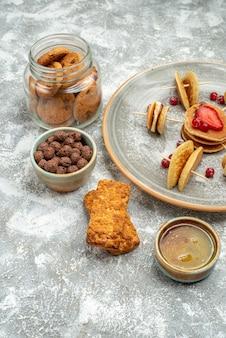Vertikale ansicht von buttermilchfruchtpfannkuchen mit keksenplätzchen und honig auf blau
