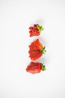 Vertikale ansicht von drei hässlich geformten erdbeeren auf dem weißen hintergrund