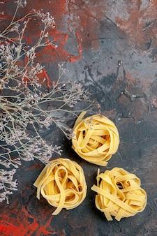 Vertikale ansicht von drei ungekochten spaggeties auf gemischtem farbhintergrund
