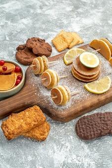 Vertikale ansicht von einfachen pfannkuchen mit zitronen auf schneidebrett und kekshonig auf blau