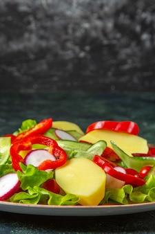 Vertikale ansicht von frisch geschälten geschnittenen kartoffeln und mit rotem pfeffer radiesiert grüne tomaten in einem braunen teller auf grünem schwarzem mischfarben-hintergrund
