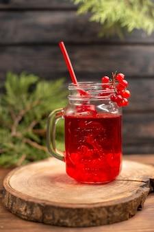 Vertikale ansicht von frischem johannisbeersaft in einem glas serviert mit rohr auf einem holzbrett cutting