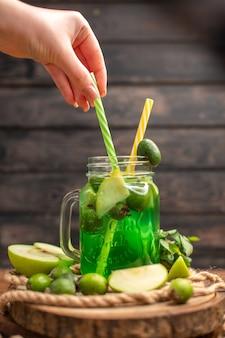 Vertikale ansicht von frischem, köstlichem fruchtsaft, serviert mit apfel- und feijoas-hand, die rohr auf einem holzbrett auf einem braunen tisch hält