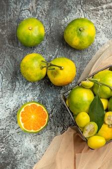 Vertikale ansicht von frischen kumquats und zitronen in einem schwarzen korb auf handtuch und vier zitronen auf grauem hintergrund