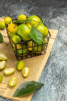 Vertikale ansicht von frischen kumquats und zitronen in einem schwarzen korb auf zeitungen auf grauem hintergrund