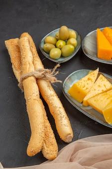 Vertikale ansicht von frischen leckeren käsescheiben auf einem handtuch und grünen oliven auf schwarzem hintergrund