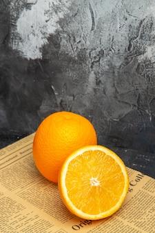 Vertikale ansicht von frischen orangen in geschnittener und ganzer form auf zeitung auf grauem hintergrund