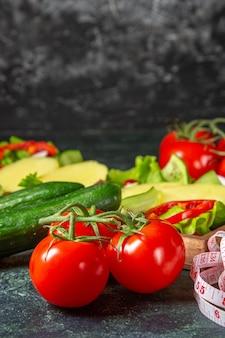 Vertikale ansicht von frischen tomaten des gehackten gemüses mit stielmesser und gurken auf einem holztablett auf mischfarbenoberfläche
