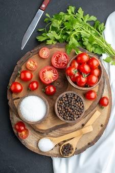 Vertikale ansicht von frischen tomaten und gewürzen in schalenlöffeln auf holzbrett auf schwarzer oberfläche