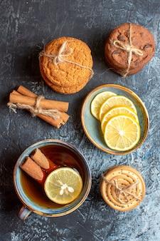 Vertikale ansicht von frischen zitronen und einer tasse schwarzem tee mit zimt verschiedene geheftete kekse auf dunklem tisch
