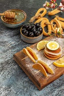 Vertikale ansicht von fruchtpfannkuchenplätzchen nahe honig in einer schüssel und schwarzen kirschen auf grauem tisch