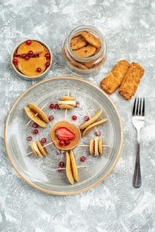 Vertikale ansicht von fruchtpfannkuchenplätzchen und -kuchen für frühstück auf blau