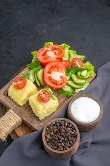 Vertikale ansicht von gehacktem frischem gemüsekäse auf schneidebrett und gewürzen auf dunklem handtuch auf schwarzer oberfläche