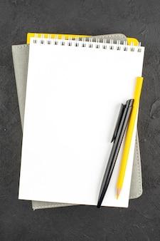 Vertikale ansicht von geschlossenen spiralnotizbüchern und kugelschreiber auf schwarz