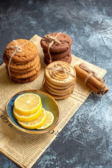 Vertikale ansicht von gestapelten leckeren keksen zimt zitrone auf einer alten zeitung auf dunklem hintergrund