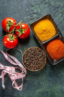 Vertikale ansicht von gewürzschalen erfüllt mit rotem pfeffer und gelbem ingwer meter frische tomaten mit stiel auf mischfarben oberfläche