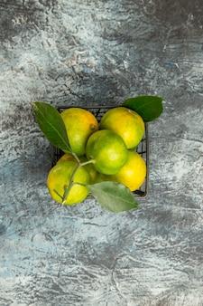 Vertikale ansicht von grünen mandarinen mit blättern in einem korb auf grauem hintergrund über der ansicht stockfoto