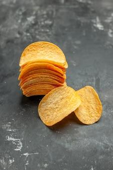 Vertikale ansicht von hausgemachten gestapelten kartoffelchips auf grauem hintergrund