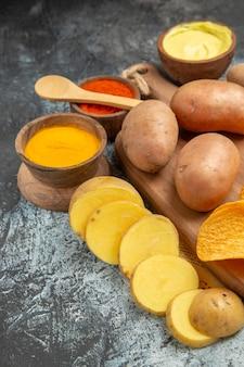 Vertikale ansicht von hausgemachten köstlichen kartoffelchips auf hölzernem schneidebrett