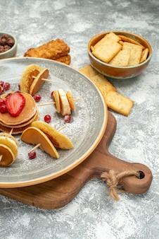 Vertikale ansicht von hausgemachten pfannkuchen und keksen auf holzschneidebrett auf blauem hintergrund