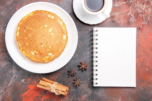 Vertikale ansicht von hausgemachten pfannkuchen zimt limette eine tasse tee und notizbuch auf gemischten farbtisch