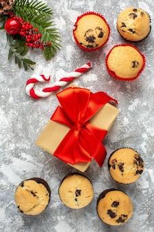 Vertikale ansicht von kleinen cupcakes weihnachtsgeschenke mit rotem band und süßigkeiten tannenzweigen auf eisoberfläche