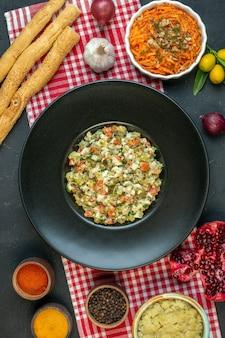 Vertikale ansicht von köstlichem salat knoblauch paprika salat granatäpfel kumquats mit stiel auf dunklem hintergrund