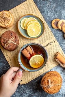 Vertikale ansicht von köstlichen keksen und hand, die eine tasse schwarzen tee mit zimt auf einer alten zeitung auf dunklem hintergrund hält