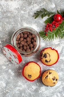 Vertikale ansicht von köstlichen kleinen cupcakes und schokolade in einem glastopf und tannenzweigen auf eisoberfläche