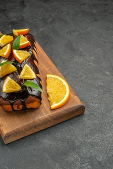 Vertikale ansicht von leckeren kuchen verziert mit zitrone und schokolade auf schneidebrett auf schwarzem tisch