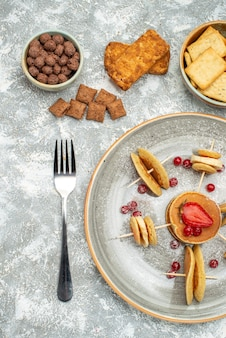 Vertikale ansicht von leckeren pfannkuchen mit schokolade und keksen auf blauem hintergrund