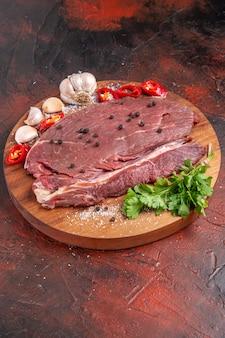 Vertikale ansicht von rotem fleisch auf holztablett und knoblauch, grüne zitronenzwiebelgabel und -messer auf dunklem hintergrund