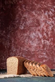 Vertikale ansicht von schwarzbrotscheiben auf nacktem farbtuch auf kastanienbraunem hintergrund
