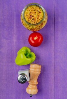 Vertikale ansicht von spaghetti-makkaroni mit tomatenpfeffersalz auf lila tabelle