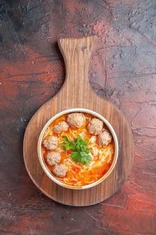 Vertikale ansicht von tomaten-fleischbällchen-suppe mit nudeln in einer braunen schüssel auf dunklem hintergrund