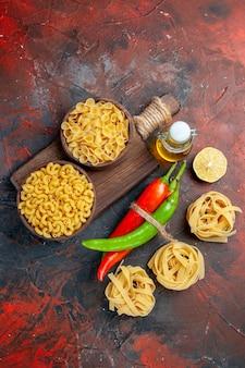 Vertikale ansicht von ungekochten nudeln cayennepfeffer, die ineinander mit seilölflasche zitrone oder knoblauch auf gemischtem farbhintergrund gebunden sind
