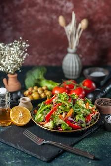 Vertikale ansicht von veganem salat mit frischen zutaten in einem teller auf schwarzem schneidebrett